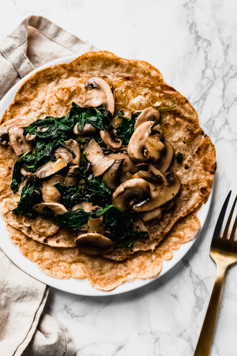 overhead close-up view of a plate of oat crepes with sautéed mushrooms and spinach with a fork