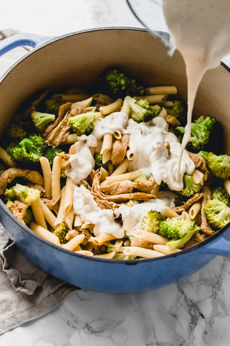 cashew alfredo sauce poured into a pot of pasta and broccoli