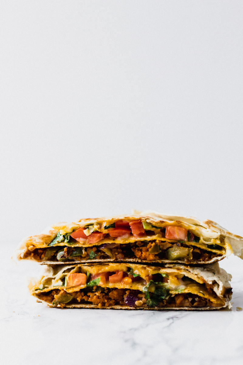 two halves of a tortilla filled with vegan meat, cheese, and vegetables cut in half