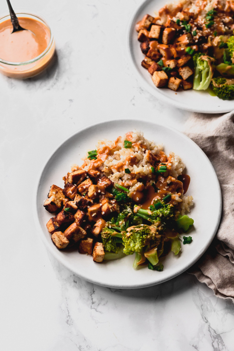 side view of two plates with brown grains, crispy fried tofu, and steamed broccoli drizzled with peanut sauce