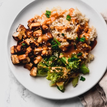 close up of a brown rice bowl with fried tofu, broccoli, peanut sauce, sesame seeds, and green onions