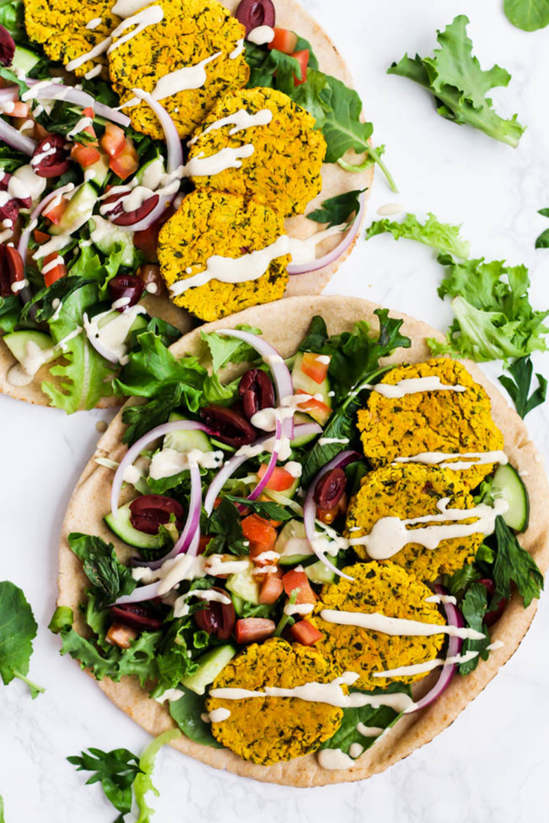 Two pitas topped with lettuce, olives, cucumber slides, red onion, chopped tomatoes and four turmeric falafels each. The pita sandwiches are topped with a tahini drizzle