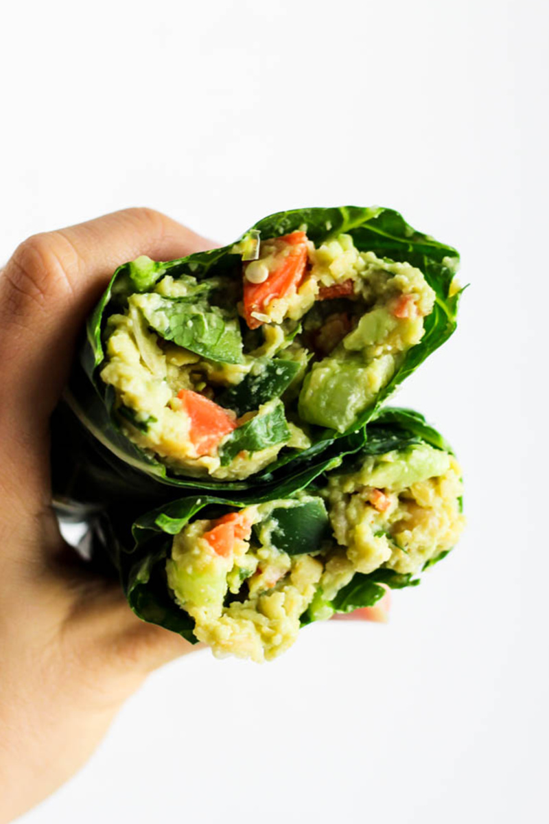 An avocado chickpea salad served in a collard wrap. A hand holds both halves of the wrap showcasing the filling