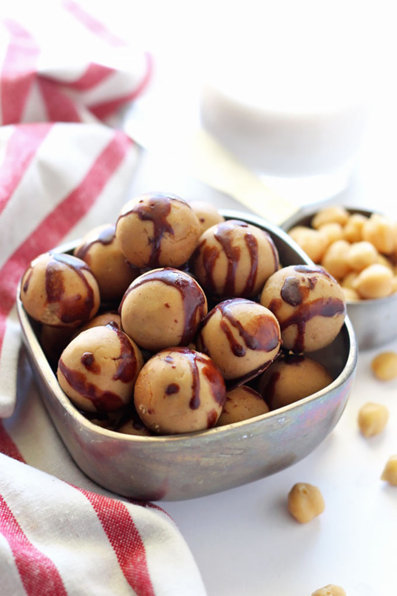 A bowl of chickpea protein balls covered in a drizzle of chocolate
