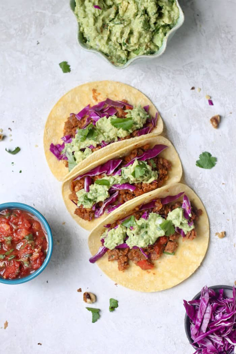Three vegan walnut and chickpea tacos on a gray stone countertop. The tacos are topped with guacamole and purple cabbage. A bowl of guacamole, a bowl of red cabbage and a bowl of salsa surround the tacos