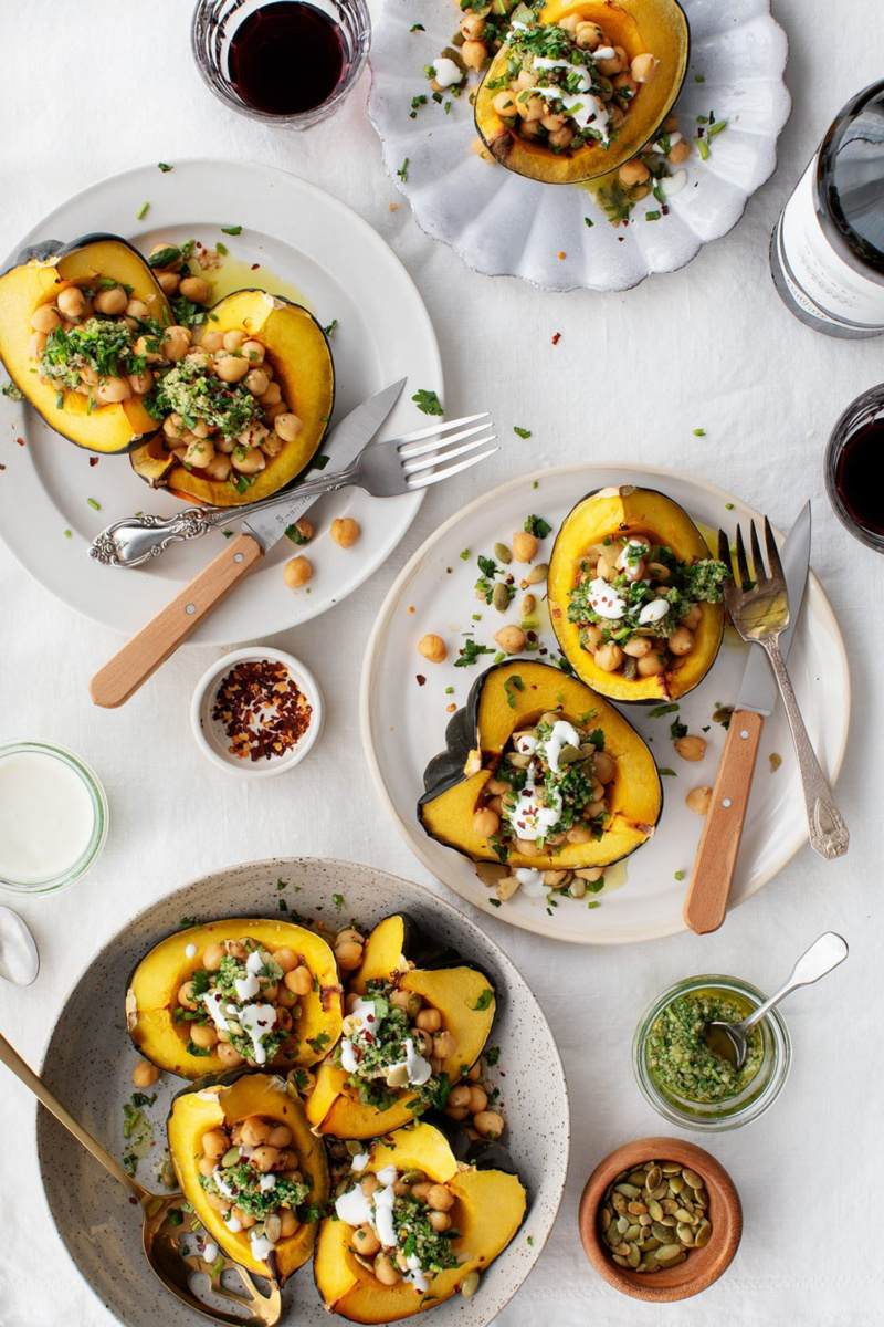 An overhead shot of four plates, each with servings of quartered acorn squashes stuffed with chickpeas, chimichurri and some topped with yogurt. Bowls of chili flakes, pumpkin seeds, chimichurri and yogurt along with two glasses of red wine surround the plates