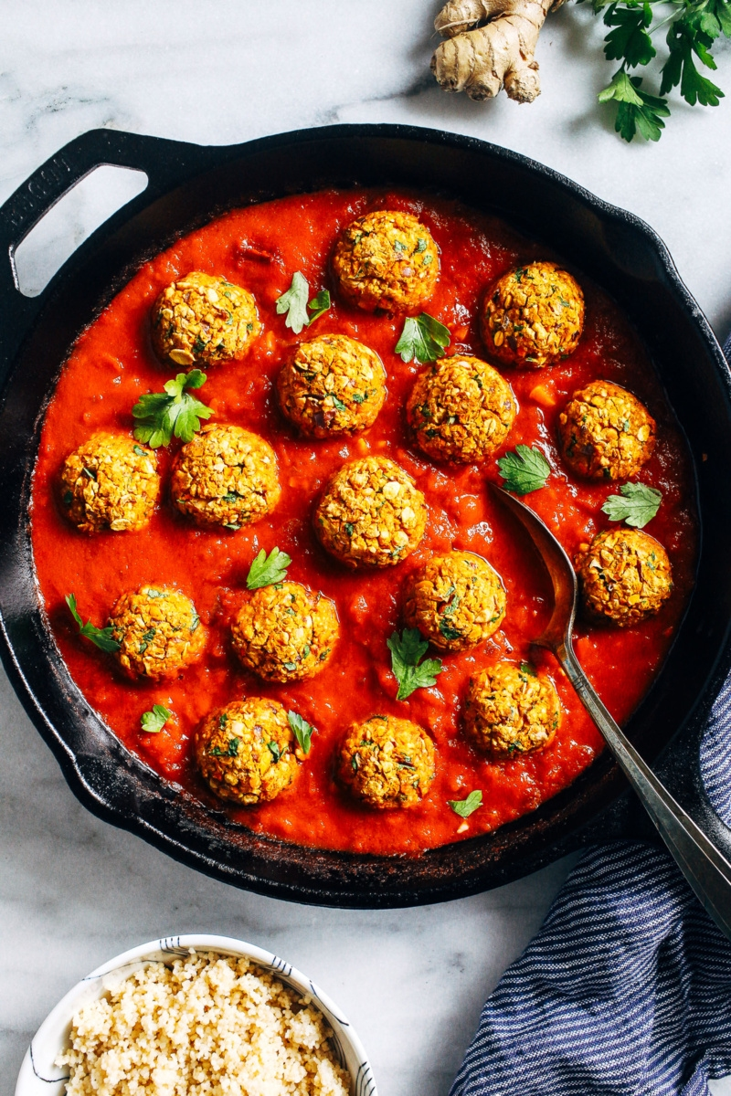 A cast iron skillet serving a red Moroccan sauce and chickpea meatballs. The sauce is topped with sprigs of cilantro. A small bowl of quinoa, a knob of ginger and a spring of cilantro surround the skillet