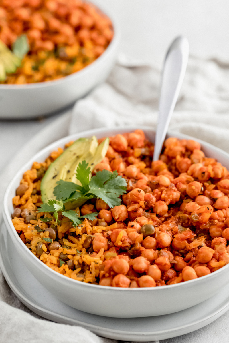 A bowl of chickpeas in sofrito served with arroz con grandules. The dish is topped with avocado slices and a sprig of cilantro