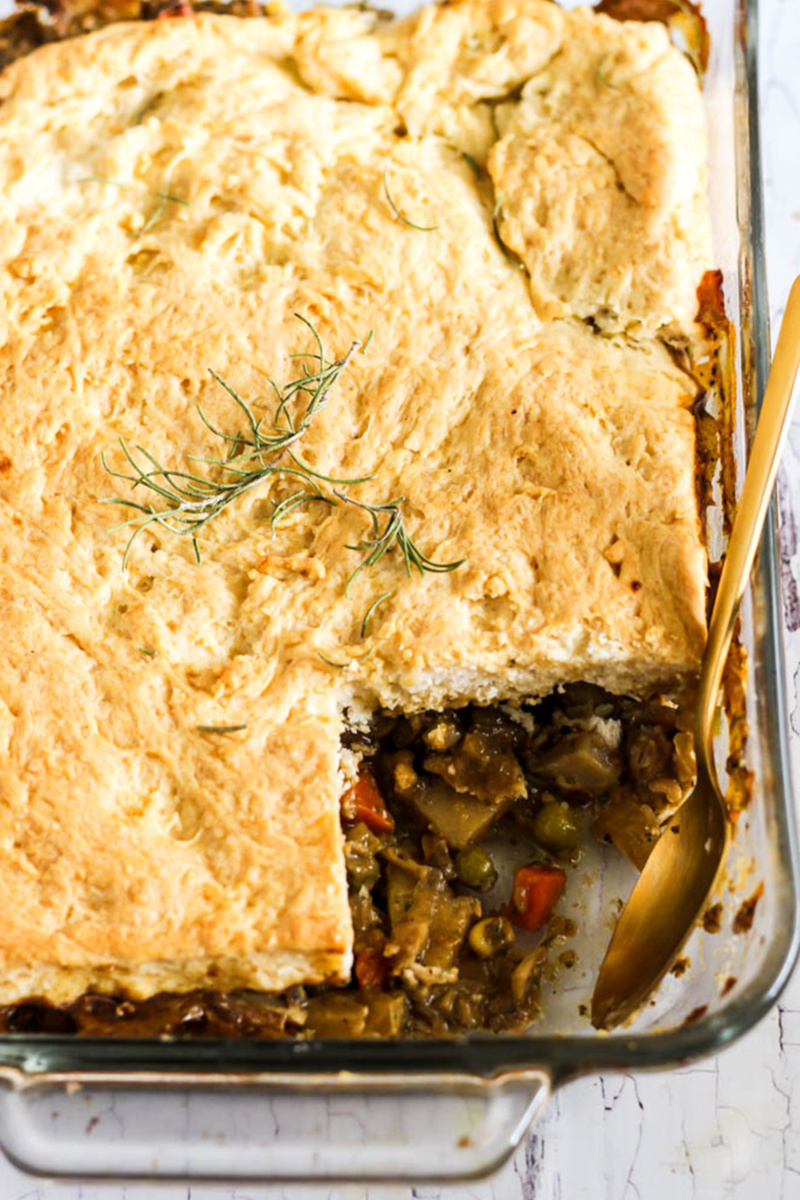 A chickpea pot pie served in a casserole dish. One scoop has been served from the pot pie, revealing the vegetable filling