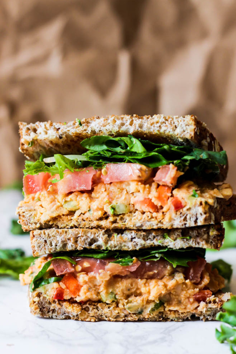 Two halves of a buffalo chickpea sandwich stacked on top of one another. The sandwich is topped with lettuce and tomato