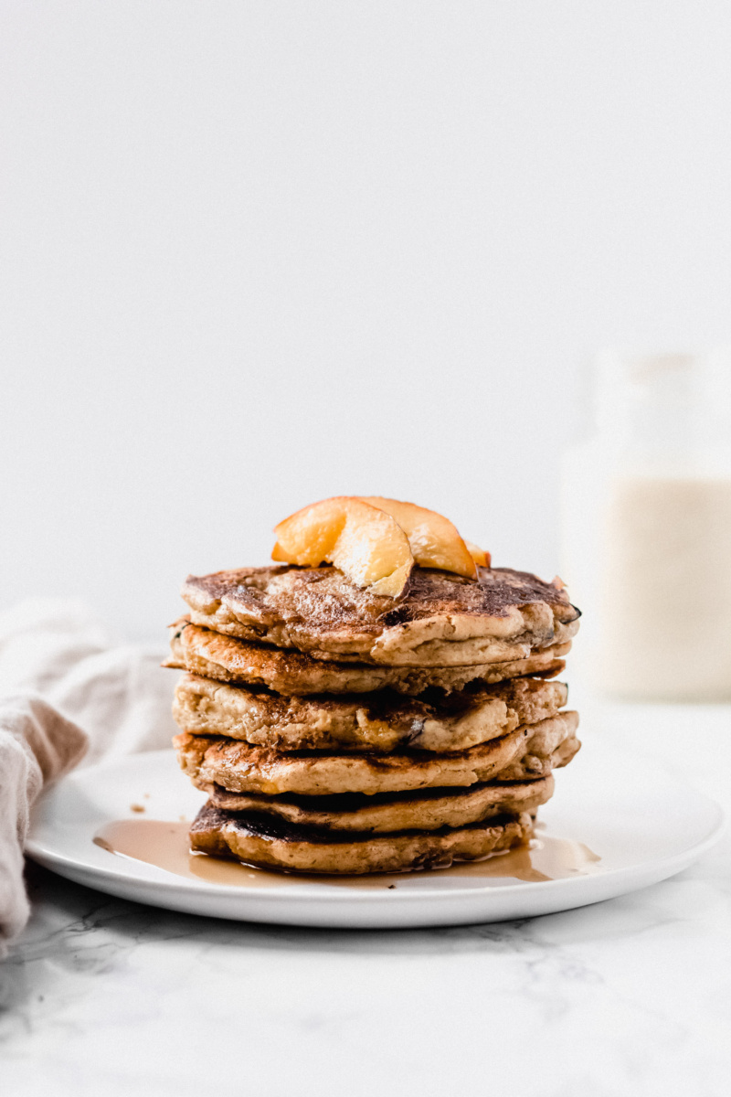 a stack of pancakes with sliced peaches and maple syrup on top