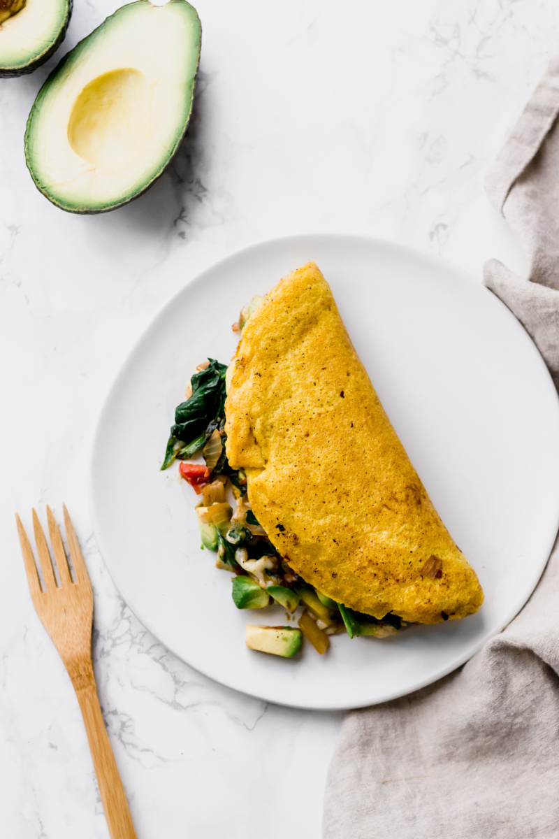 yellow omelette folded in half with vegetables and cheese inside
