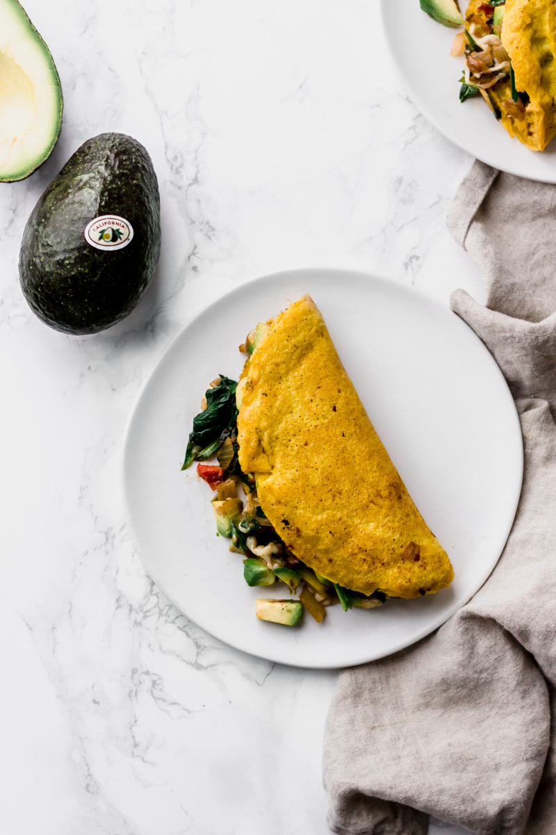 omelette stuffed with vegetables with a whole avocado on the side