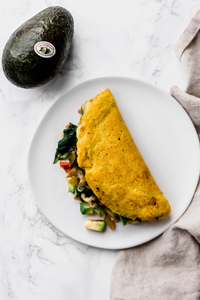close up of an omelette stuffed with vegetables with a whole avocado on the side
