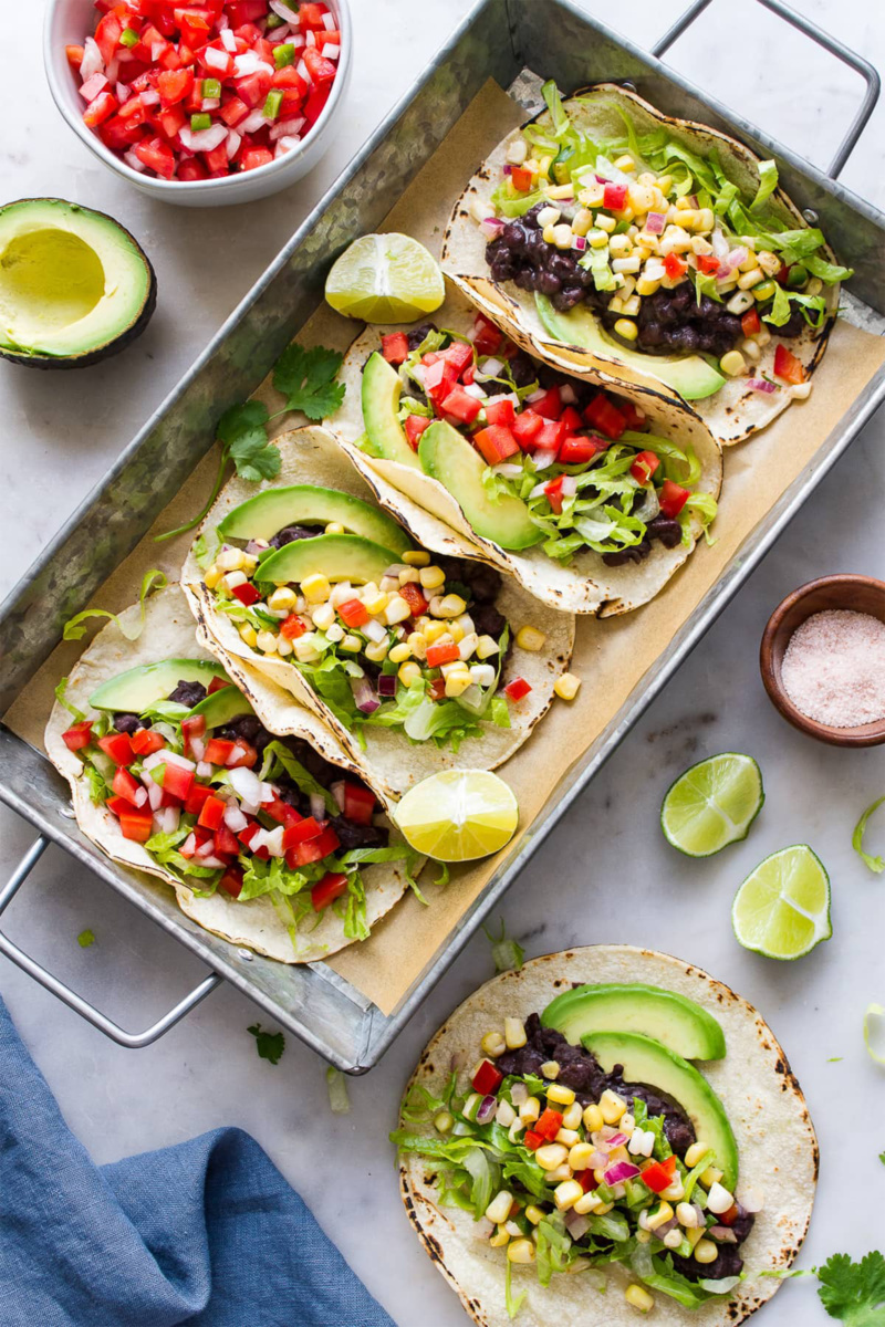 a tray of corn and black bean tacos served with limes
