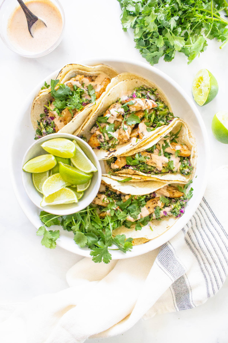 a plate of vegan chicken tacos served with limes