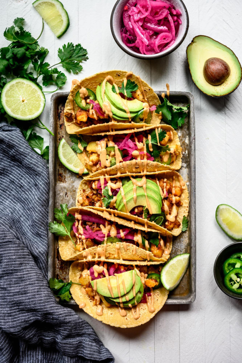 a tray of vegan tacos topped with avocado and cilantro