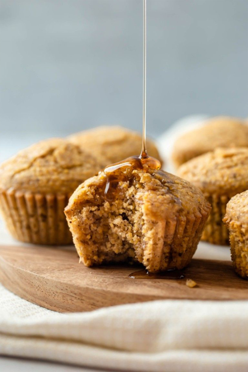 Maple syrup being drizzled on top of a vegan cornbread muffin with a bite taken out of it
