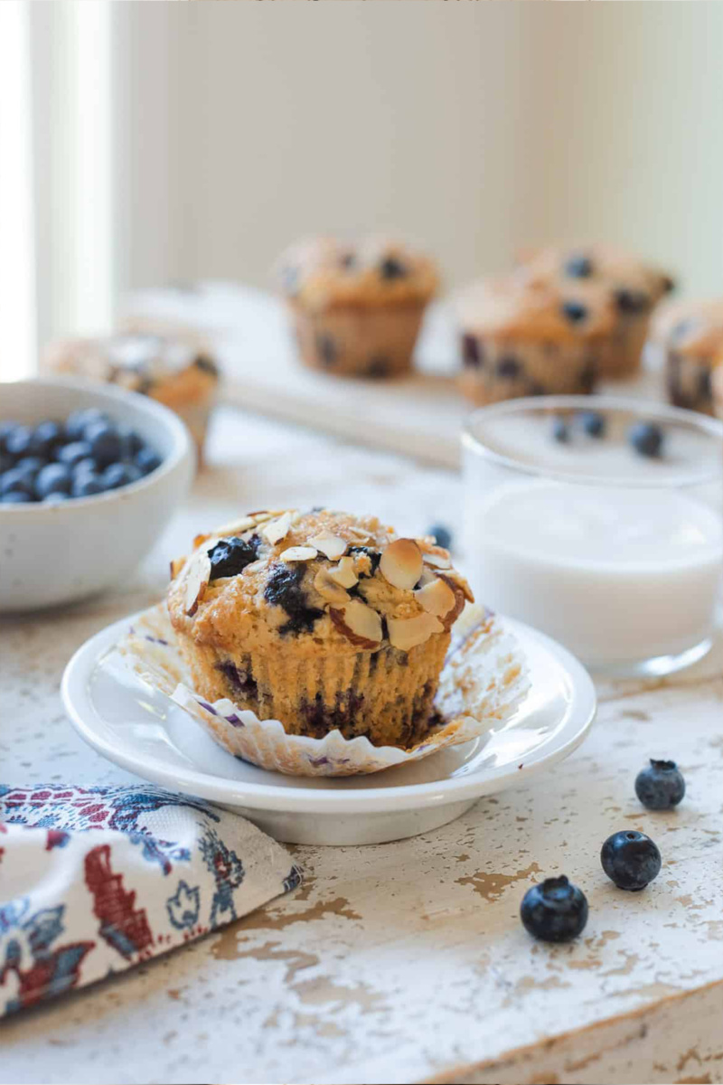 A blueberry almond muffin sits on a small white plate alongside a glass of plant-based milk