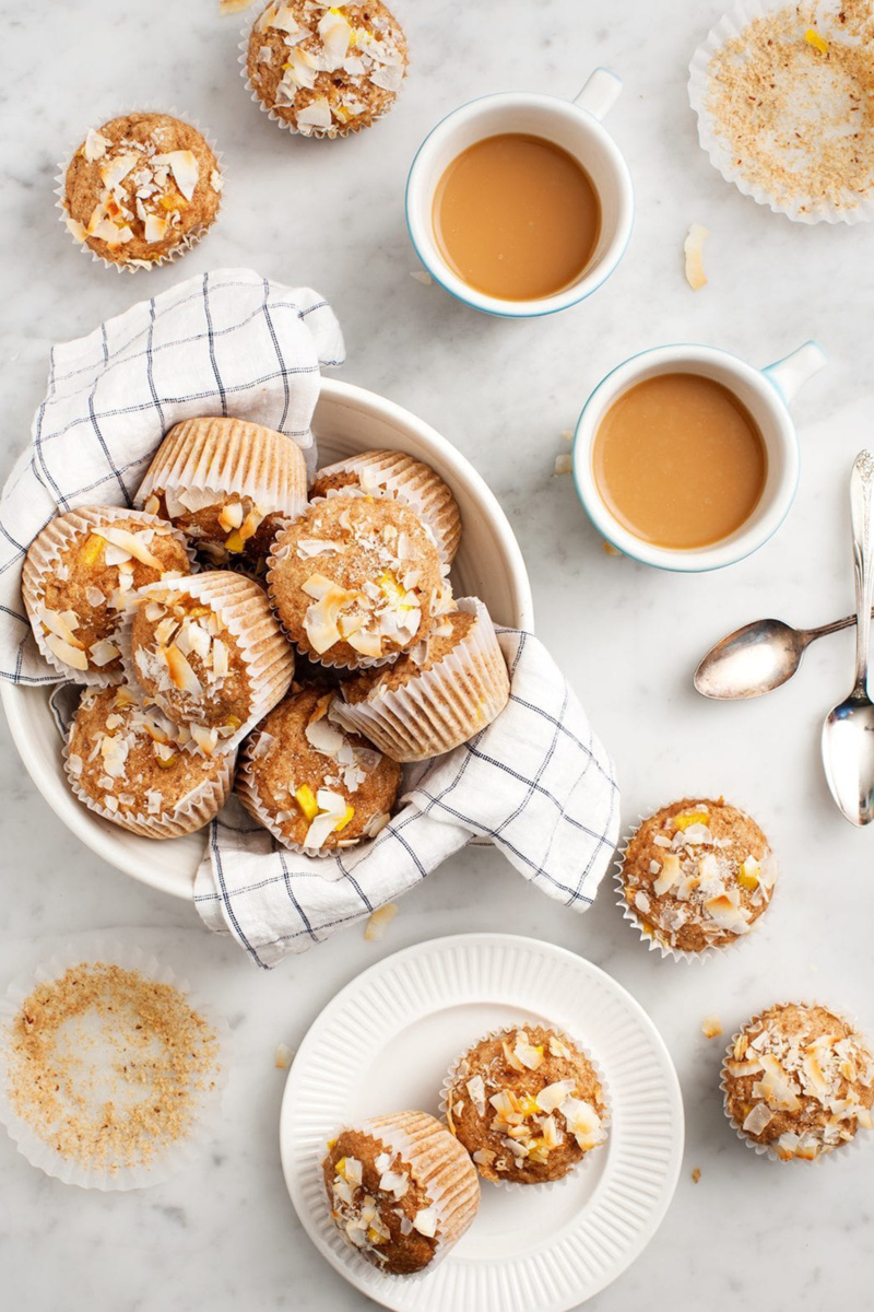 Mango coconut muffins served in a white bowl alongside two cups of coffee