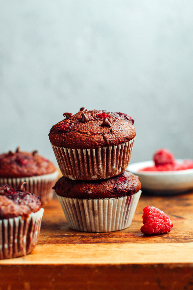 Two chocolate raspberry muffins are stacked on top of one another