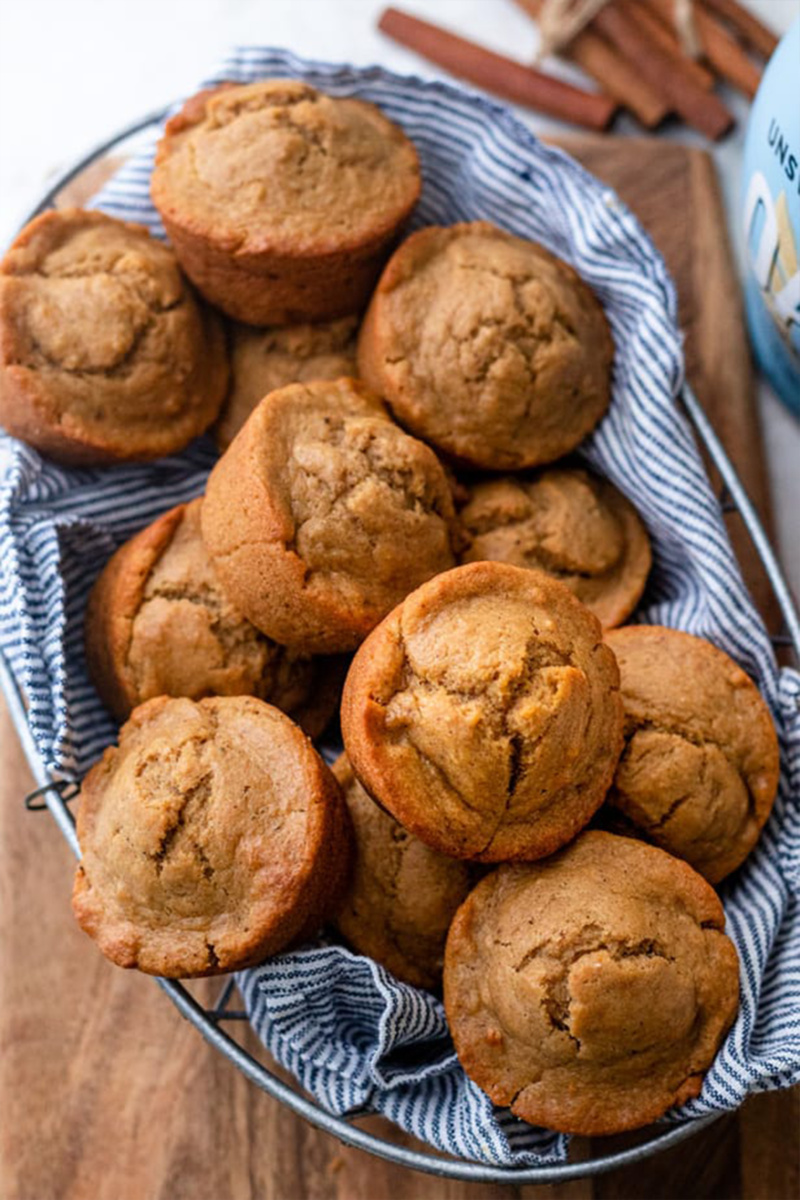 A basket lined with a blue and white striped towel is filled with chai spiced muffins
