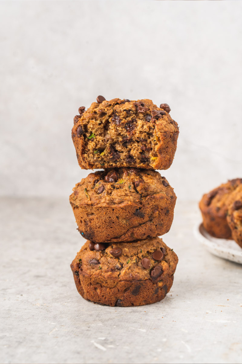 Three zucchini chocolate chip muffins stacked on top of one another