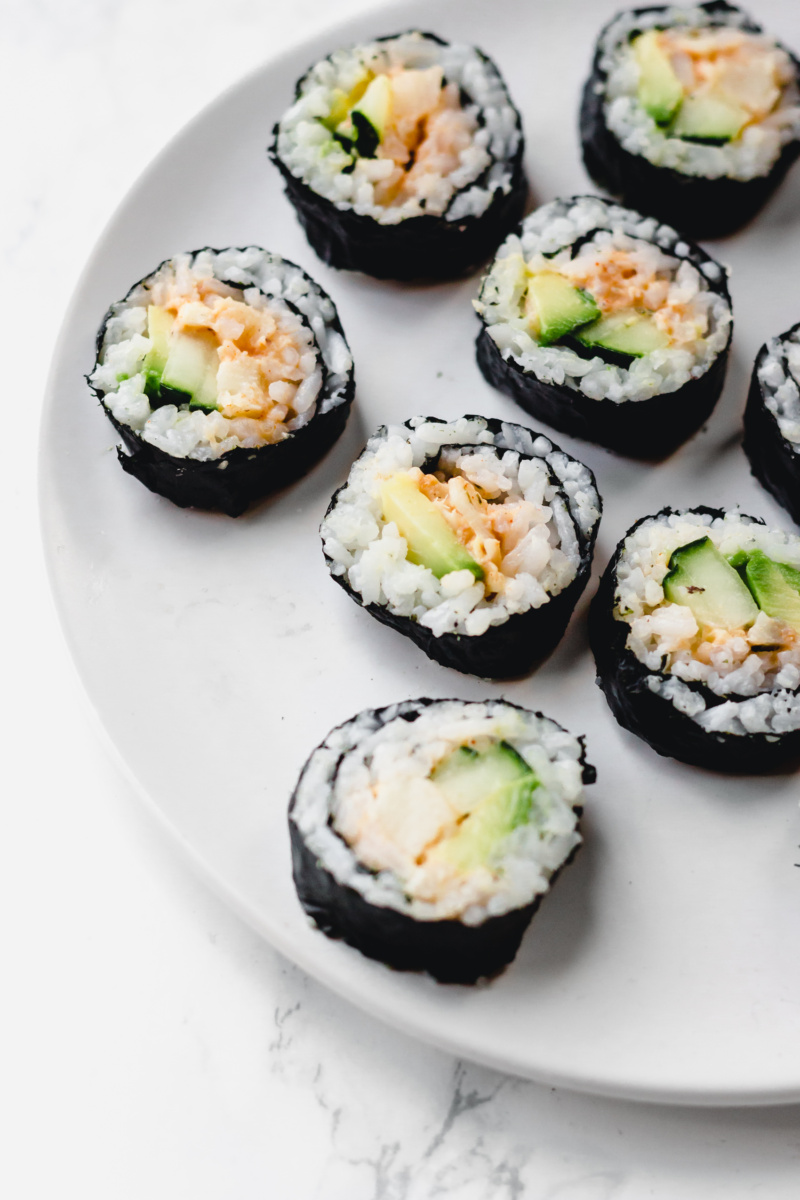 a plate of vegan California roll slices, filled with avocado, cucumber and hearts of palm