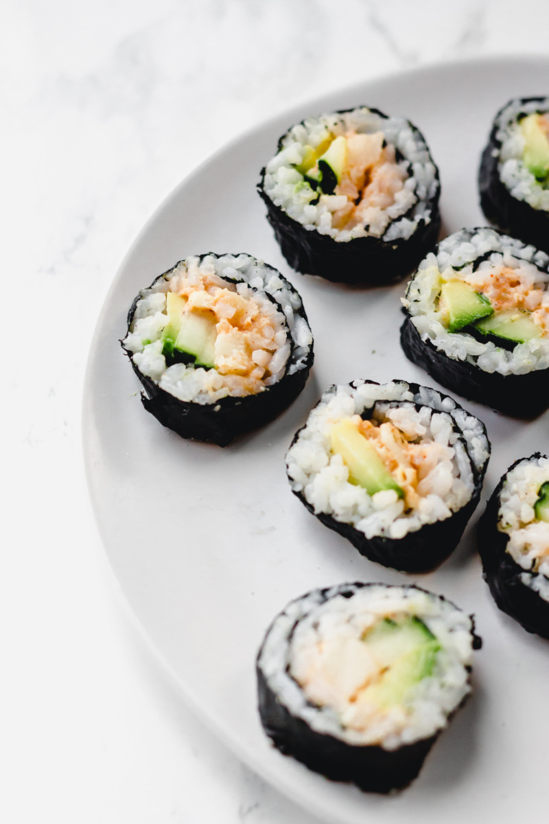 a close up of a plate of vegan sushi cut into slices. The sushi is fulled with avocado, cucumber and hearts of palm