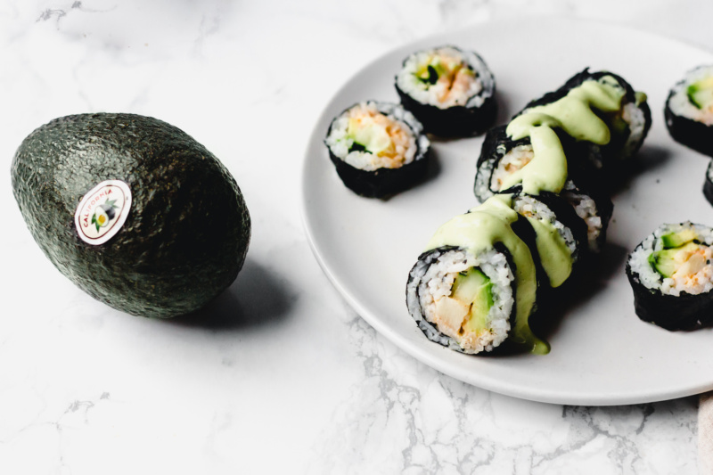 an avocado sits alongside a plate of vegan california roll slices topped with an avocado wasabi sauce