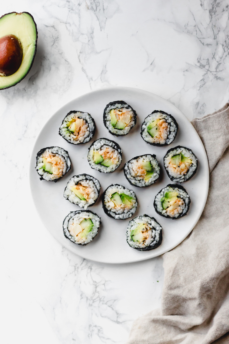 A plate of sliced vegan sushi made with cucumber, avocado and hearts of palm served alongside half of an avocado