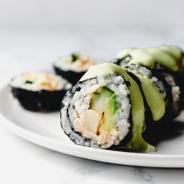 a close up of a vegan sushi roll filled with hearts of palm, avocado and cucumber and topped off with a drizzle of avocado wasabi sauce