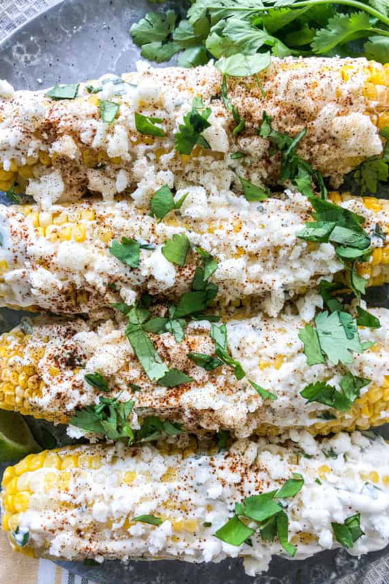 Four Mexican street corn cobs topped with chopped cilantro