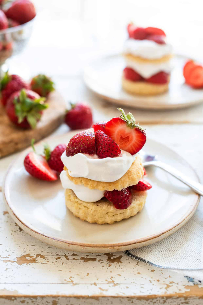 a strawberry shortcake topped with vegan whipped cream and fresh strawberries
