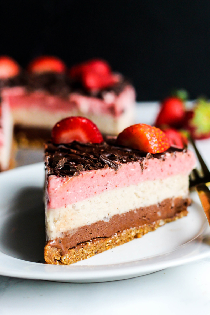 vegan Neapolitan ice cream cake topped with a drizzle of melted chocolate and fresh strawberries
