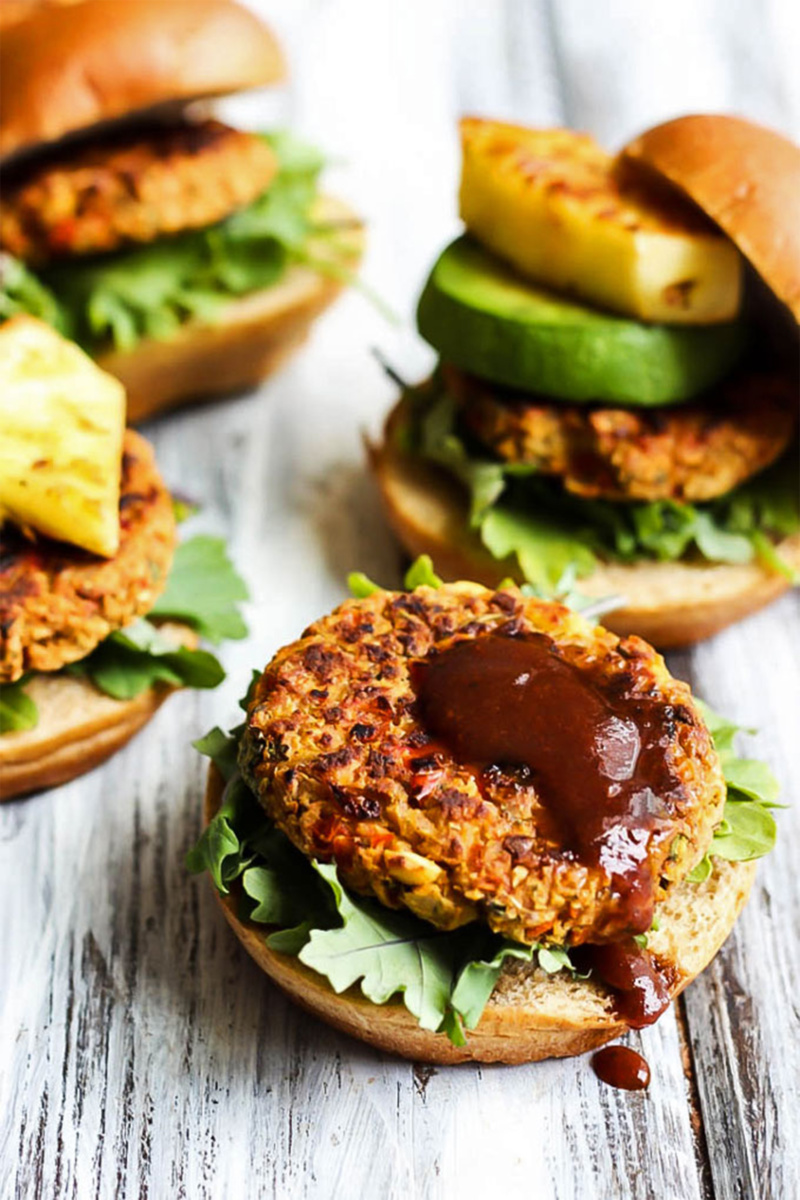 Hawaiian chickpea veggie burgers topped with lettuce, avocado, bbq sauce and pineapple slices