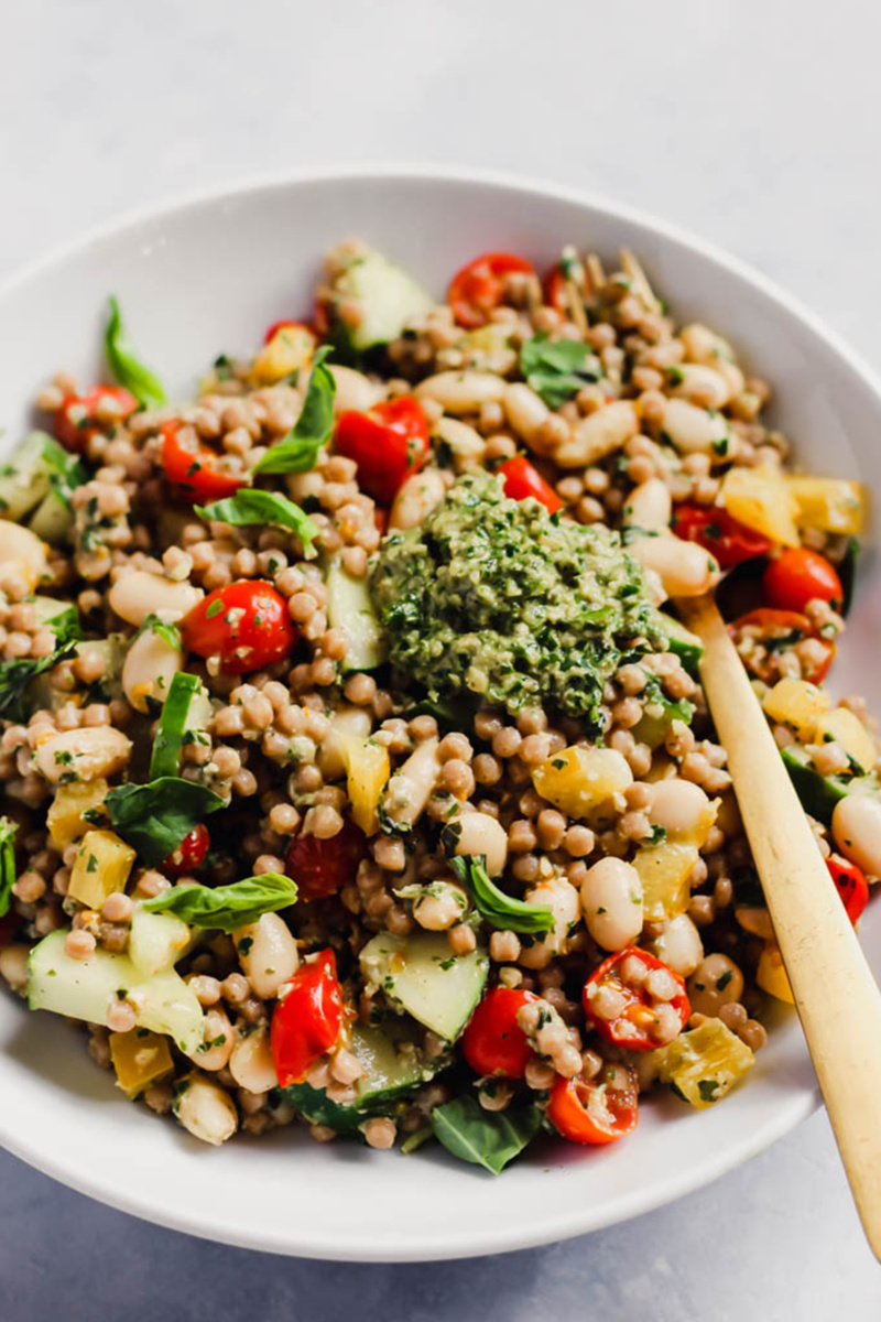 vegan pesto couscous salad with tomatoes, sliced vegetables and a dollop of pesto