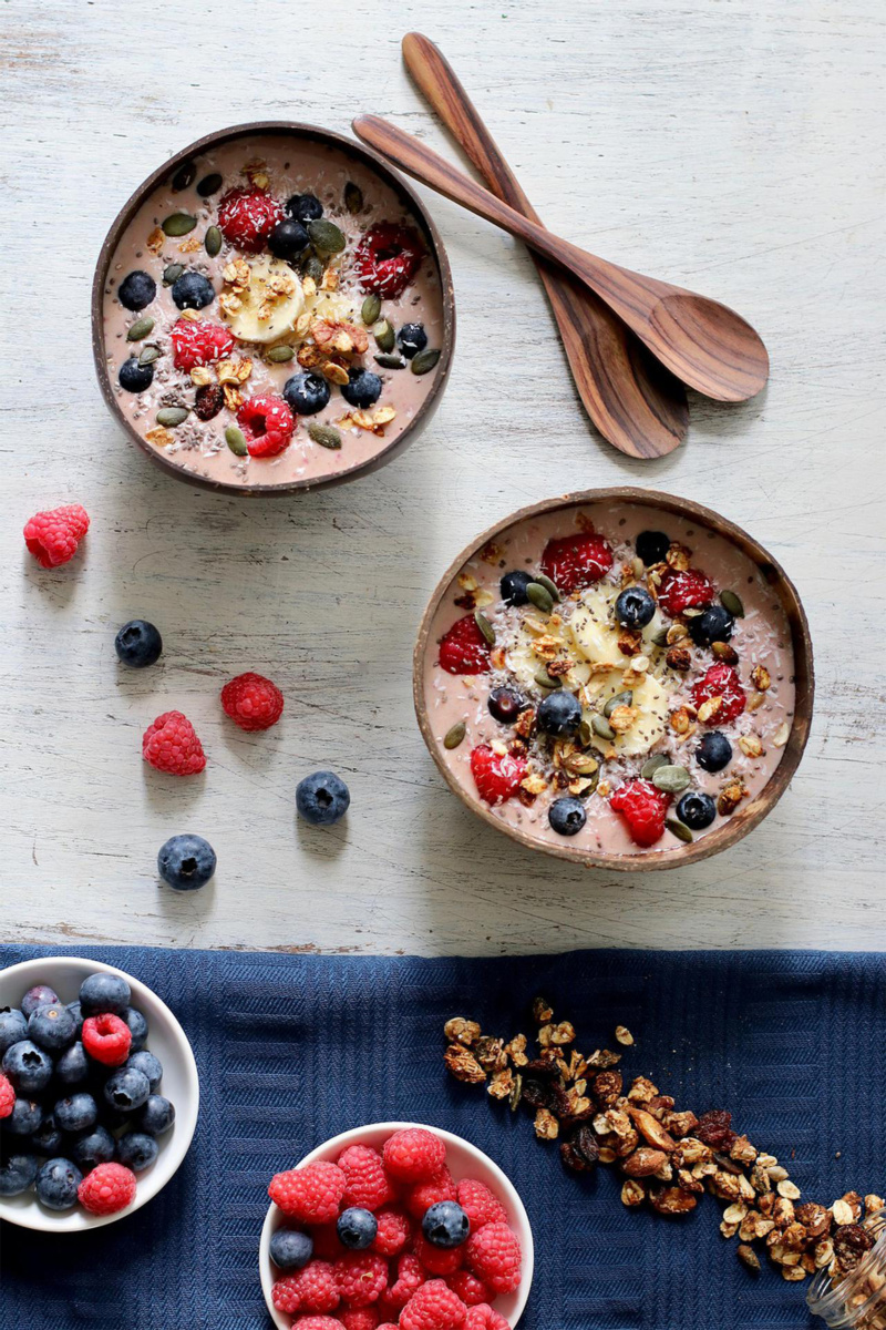 two bowls of peanut butter and berry smoothie bowl topped with fresh berries, seeds and sliced banana