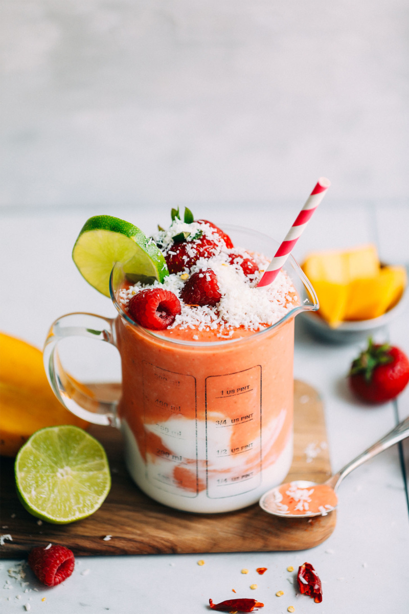 a berry smoothie with coconut cream topped with fresh coconut, berries and a slice of lime