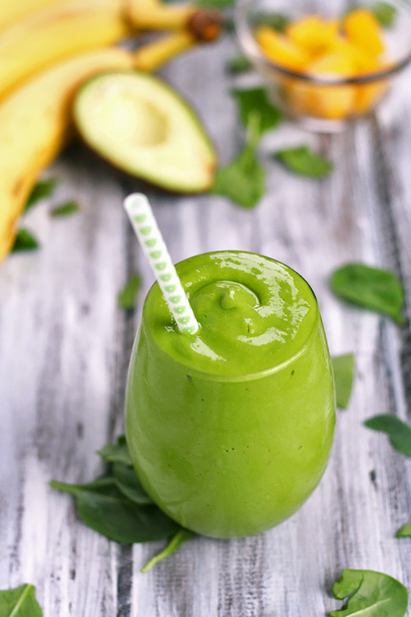 a green smoothie surrounded by avocado and a banana