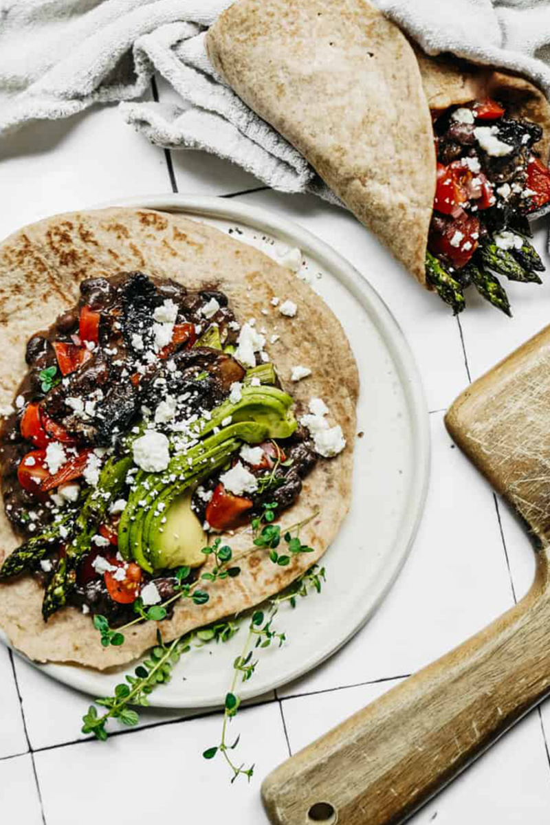 a tortilla filled with vegetables, avocado and vegan cheese