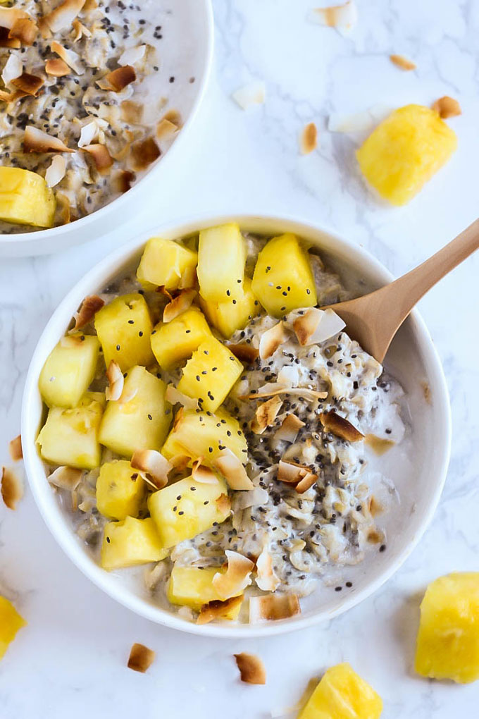 a bowl of overnight oats topped with toasted coconut and pineapple
