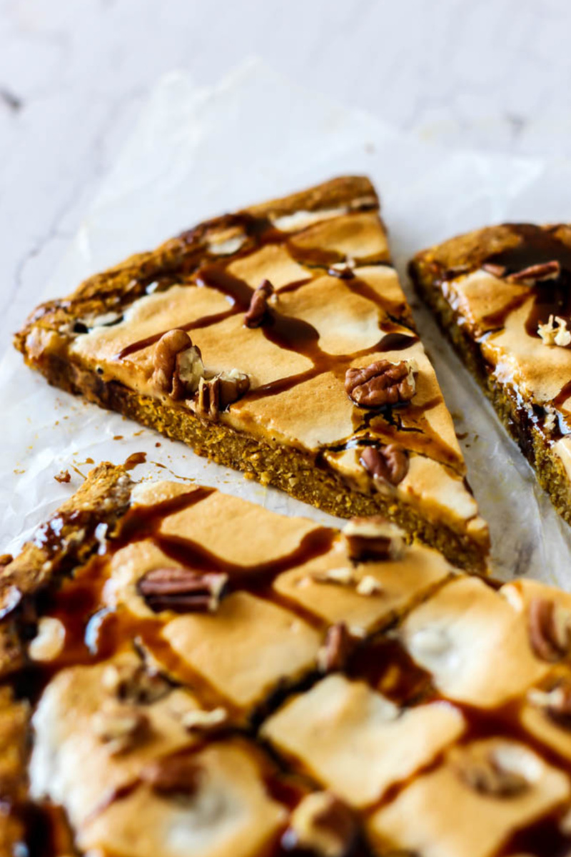 a pumpkin dessert pizza topped with chocolate sauce and pecans