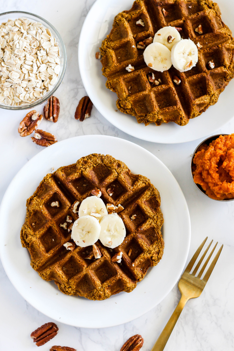 two plates of pumpkin waffles topped with bananas and pecans